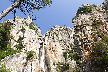 Blue sky frames The Piscia di Gallo waterfall surrounded by granite rocks, Zonza, Southern Corsica, France, Europe