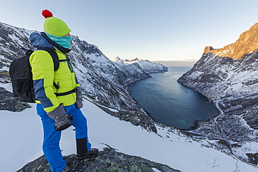 Hiker on top of the crest admires the village of Fjordgard framed by the frozen sea of the Ornfjorden, Senja, Troms, Norway, Scandinavia, Europe