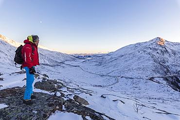 Hiker on top of the rocky crest admires the snowy peaks of Fjordbotn, Lysnes, Senja, Troms, Norway, Scandinavia, Europe