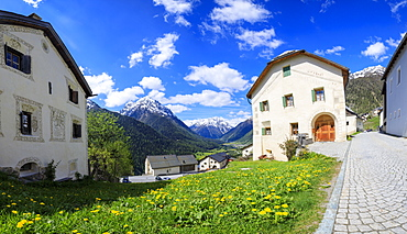 Panorama of alpine village framed by snowy peaks, Guarda, Inn District, Lower Engadine, Canton of Graudbunden, Switzerland, Europe