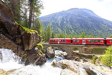 Bernina Express train beside alpine creek, Morteratsch, Engadine, Canton of Graubunden, Switzerland, Europe