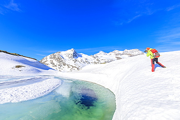 Photographer at the Bernina Pass during the spring thaw, St Moritz, Upper Engadine, Canton of Graubunden, Switzerland, Europe