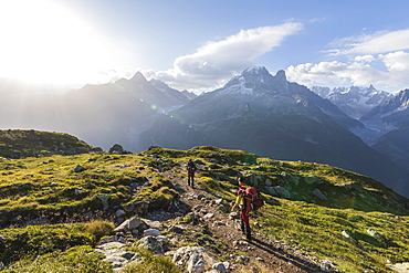 Hikers on the way to Lacs De Cheserys from Argentiere with Les Drus and Aiguille Verte in the background, Haute Savoie, French Alps, France, Europe