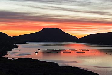Codfish tanks in the ocean at sunrise, Eidi, Nordskali fjord, Eysturoy Island, Faroe Islands, Denmark, Europe