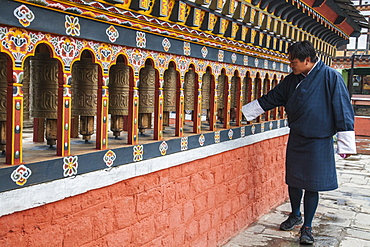 A man rotates the roller-books of the Monastery of Rinpung Dzong which are used to pray, Paro, Bhutan, Asia