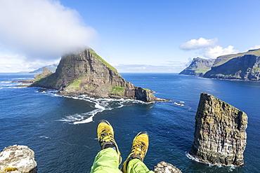 Man lays down on cliffs above the sea stacks of Drangarnir and Tindholmur islet, Vagar Island, Faroe Islands, Denmark, Europe