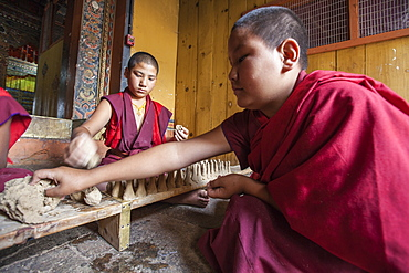 Young Buddhist monk takes clay with his hand to create objects that will be sold for the upkeep of the monastery, Punakha, Bhutan, Asia