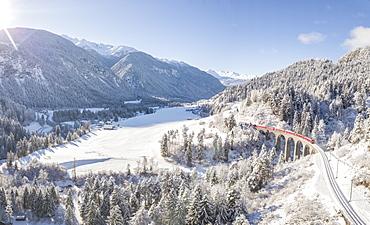 Panoramic of Bernina Express train on Landwasser Viadukt, UNESCO World Heritage Site, Filisur, Albula Valley, Canton of Graubunden, Switzerland, Europe (Drone)