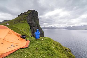 Hiker and tent on cliffs around Kallur Lighthouse, Kalsoy Island, Faroe Islands, Denmark, Europe