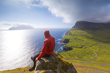 Hiker sitting on rocks looking at the ocean, Gasadalur, Vagar Island, Faroe Islands, Denmark, Europe