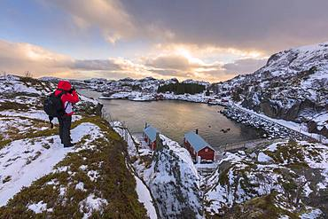 Photographer on rocky peak, Nusfjord, Lofoten Islands, Nordland, Norway, Europe