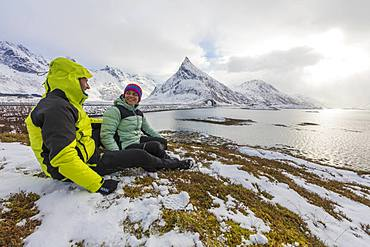 Hikers on meadows covered with snow with Volanstinden in the background, Fredvang, Lofoten Islands, Nordland, Norway, Europe