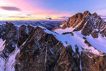 Aerial view of helicopter in flight towards Piz Roseg at sunset, Bernina Group, border of Italy and Switzerland, Europe