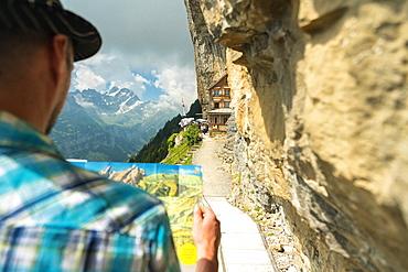 Man looks at map of hiking trails, Aescher-Wildkirchli Gasthaus, Ebenalp, Appenzell Innerrhoden, Switzerland, Europe