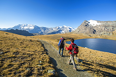 Hikers wallking along Rosset Lake, Gran Paradiso National Park, Alpi Graie (Graian Alps), Italy, Europe