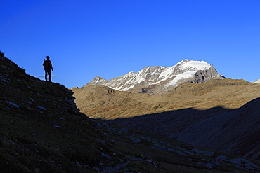 Hiker admires the view of Alpi Graie (Graian Alps) landscape, Gran Paradiso National Park, Italy, Europe