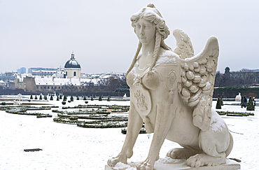Mythological statue in the snow covered Belvedere Garten, gardens of castle housing an art museum, Vienna, Austria, Europe