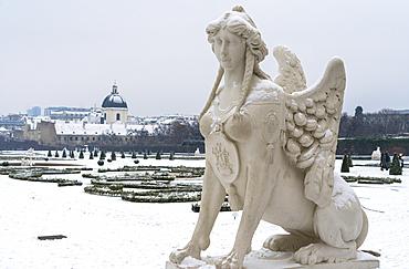 Mythological statue in the snow covered Belvedere Garten, gardens of castle housing an art museum, Vienna, Austria, Europe