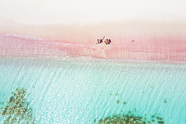 Man and woman having fun to fly a drone on pink sand beach, Caribbean, Antilles, West Indies, Central America
