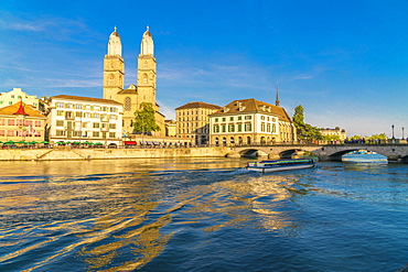 Ferry along Limmat River next to Munsterbrucke bridge with Grossmunster in background, Zurich, Switzerland, Europe