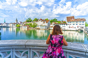Rear view of woman leaning on terrace over Limmat River admiring the old buildings of Lindenhof, Zurich, Switzerland, Europe