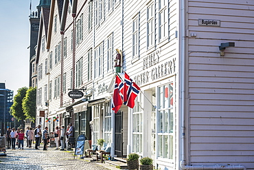 Tourists look at shops and traditional wood buildings in Bryggen old street, Bergen, Hordaland County, Norway, Scandinavia, Europe