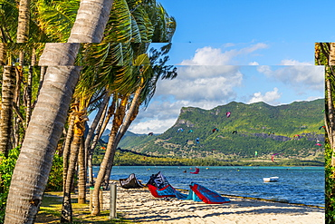 Kitesurf in the ocean seen from tropical palm-fringed beach, Le Morne Brabant, Black River district, Mauritius, Indian Ocean, Africa
