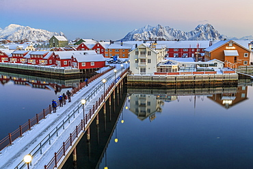 Hikers admire sunset colors on the typical red houses from a deck, Svolvaer, Lofoten Islands, Arctic, Norway, Scandinavia, Europe