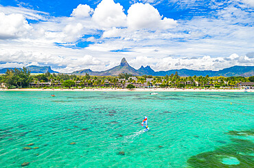 Aerial view by drone of windsurfer in the lagoon facing Flic en Flac beach and Piton de la Petite Riviere Noire mountain, Black River, Mauritius, Indian Ocean, Africa