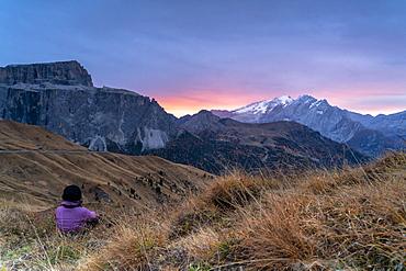 Rear view of woman sitting on grass admiring sunrise on Marmolada and Sass Pordoi, Passo Sella, Dolomites, South Tyrol, Italy, Europe