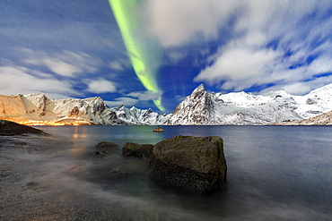 Northern Lights (aurora borealis) illuminate Hamnoy village and snowy peaks, Lofoten Islands, Arctic, Norway, Scandinavia, Europe