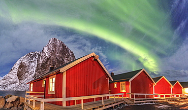 The green light of the Northern Lights (aurora borealis) lights up fishermans cabins, Hamnoy, Lofoten Islands, Arctic, Norway, Scandinavia, Europe