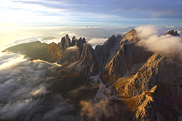 Aerial view of the mountain range of Odle surrounded by clouds in the Dolomites, Val Funes, Trentino-Alto Adige South Tyrol, Italy, Europe