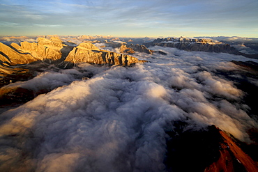 Aerial shot of Sella Group Alps surrounded by clouds at sunset in the Dolomites, Val Funes, Trentino-Alto Adige South Tyrol, Italy, Europe
