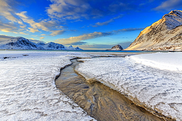 The golden sunrise reflected in a clear stream of the sea where the snow has melted, Haukland, Lofoten Islands, Arctic, Norway, Scandinavia, Europe