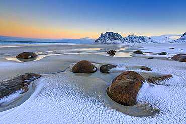 Dawn illuminates the rocks shaped by wind surrounded by fresh snow, Uttakleiv, Lofoten Islands, Arctic, Norway, Scandinavia, Europe