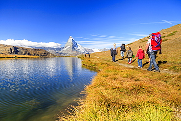 Hikers walking on the path beside the Stellisee with the Matterhorn reflected, Zermatt, Canton of Valais, Pennine Alps, Switzerland, Europe