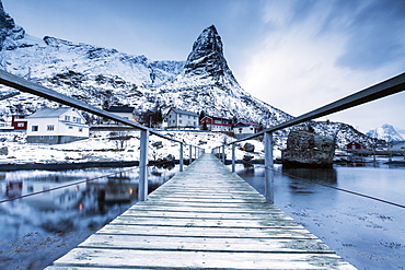 A bridge over the cold sea connects a typical fishing village. Reine, Lofoten Islands, Northern Norway, Scandinavia, Arctic, Europe