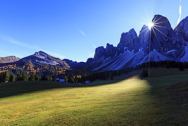 Green meadows and colorful woods in autumn frame the Odle, Malga Glatsch, Funes Valley, South Tyrol, Dolomites, Italy, Europe