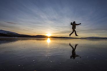 Hiker jumps on the frozen surface of Lake Limingen, Rorvik, Borgefjell National Park, Trondelag, Norway, Scandinavia, Europe