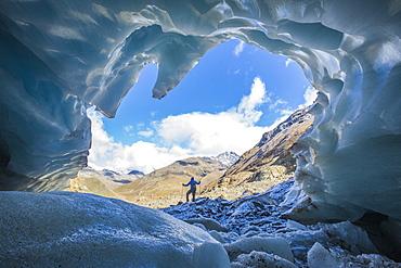 Hiker inside Forni Glacier, Forni Valley, Stelvio National Park, Valtellina, Lombardy, Italy, Europe