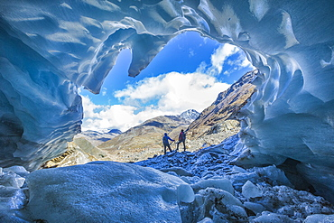 Hikers inside Forni Glacier, Forni Valley, Stelvio National Park, Valtellina, Lombardy, Italy, Europe