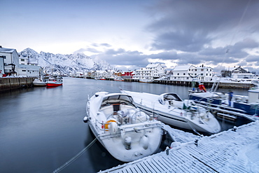 The typical fishing village of Henningsvaer surrounded by snow capped mountains and the cold sea, Lofoten Islands, Arctic, Norway, Scandinavia, Europe