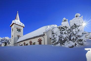 Rays of winter sun illuminate the snowy landscape and the typical church, Maloja, Engadine, Graubunden (Grisons) Canton, Switzerland, Europe