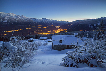 Lights of dusk illuminate the valley and the snow covered huts, Tagliate Di Sopra, Gerola Valley, Valtellina, Lombardy, Italy, Europe