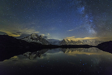 Stars and Milky Way illuminate the snowy peaks and Lac de Cheserys, Chamonix, Haute Savoie, French Alps, France, Europe