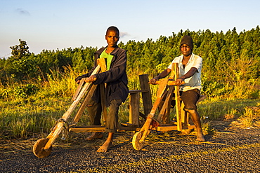 Local boys on their self-made bicycles, Malawi, Africa