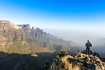 Woman enjoying the early morning sun on the cliffs, Simien Mountains National Park, UNESCO World Heritage Site, Debarq, Ethiopia, Africa