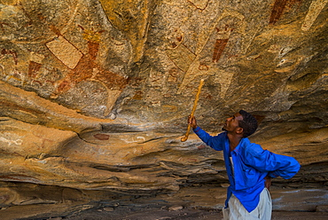 Guide pointing at cave paintings in Lass Geel caves, Somaliland, Somalia, Africa