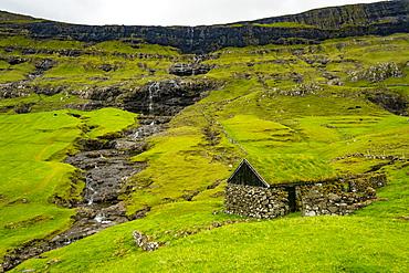 Grasstop roof house before a waterfall, Saksun, Streymoy, Faroe Islands, Denmark, Europe